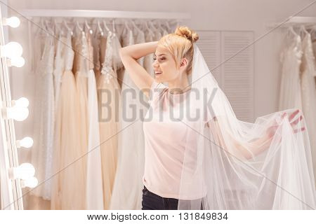 Beautiful young woman is trying on bridal veil. She is standing and looking at mirror dreamingly. The lady is smiling