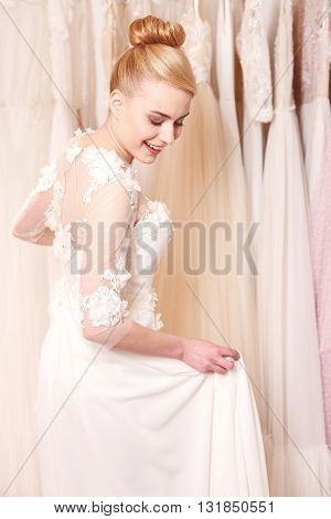 Beautiful young woman is trying on a wedding dress. She is standing in salon and smiling