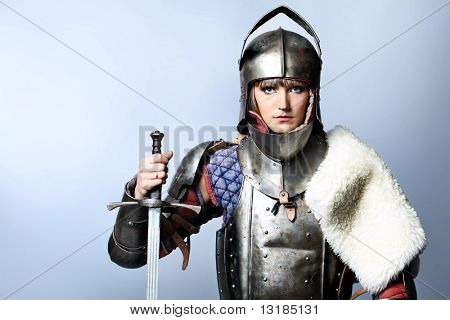 Portrait of a medieval female knight in armour over grey background.