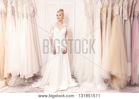 Pretty future bride is preparing for wedding. She is standing near variety of clothing hanging on rack. The lady is looking at camera and smiling