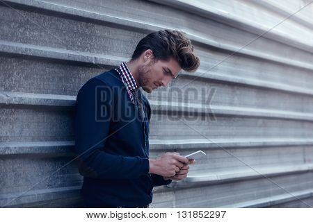 Young businessman texting smartphone phone on the street metal fence