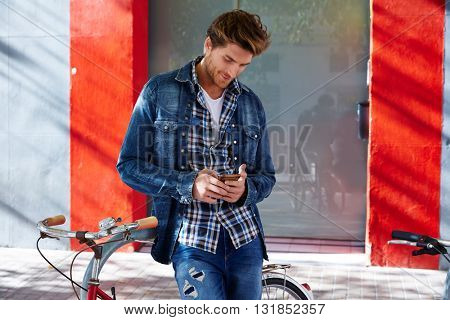 Young man using smartphone in a bicycle with jeans denim outdoor