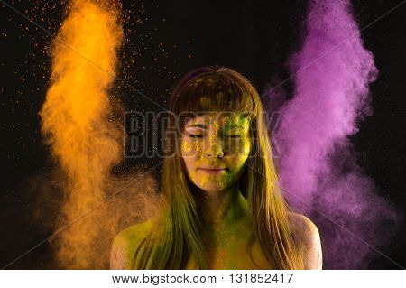 portrait woman in yellow and purple paint Holi
