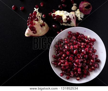 preparing a pomegranate recipe on a black stone table free space for text on the left