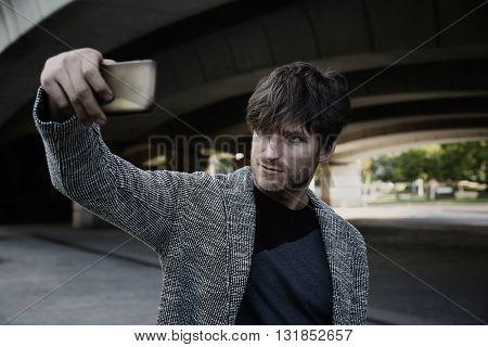 Modern young man smartphone taking selfie photos under a bridge