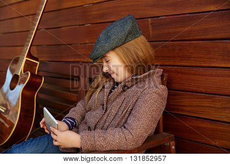 blond kid girl playing smartphone winter beret and guitar on wooden background