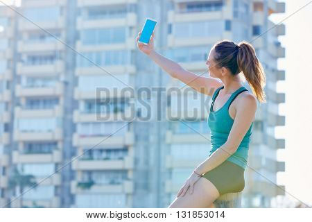 Runner girl having a rest shooting selfie with smartphone outdoor building park