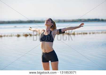 Runner woman relaxing after workout outdoor open stretching arms in a lake