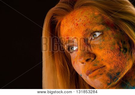 portrait face blond woman in red colors Holi closeup