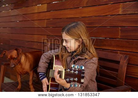 blond kid girl playing guitar with dog and winter beret on wooden background