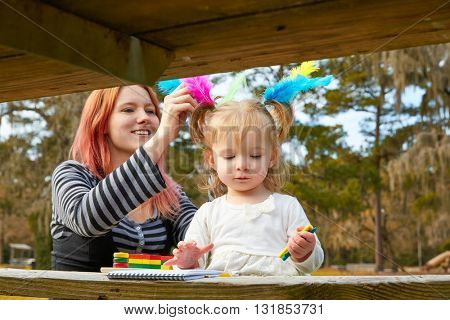 Mother and daughter drawing colors in a park lake