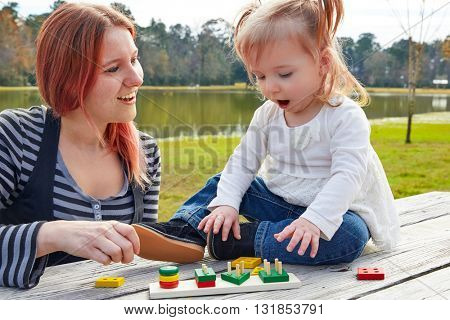 Mother and daughter playing with color shapes game in a park lake