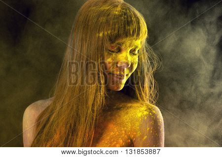 beautiful brunette in yellow colors Holi in studio