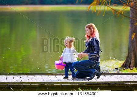 Kid girl and mother with basket playing in the park lake