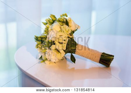 Beautiful wedding bouquet on the white piano