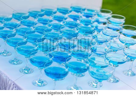 Glasses of blue champagne on the table