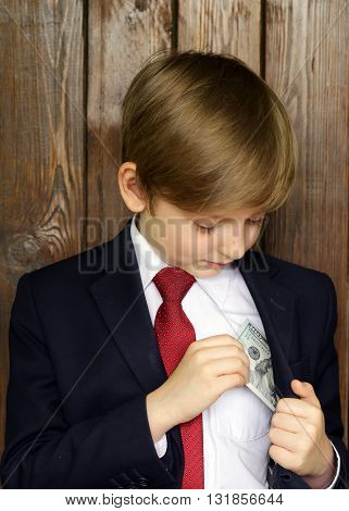 Boy in a suit with cash dollars - business concept