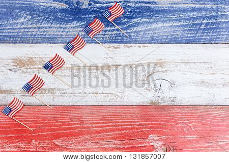Small USA flags stacked in rising formation on red white and blue rustic boards. Fourth of July holiday concept for United States of America.