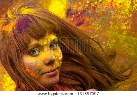 woman face in colors Holi closeup in studio