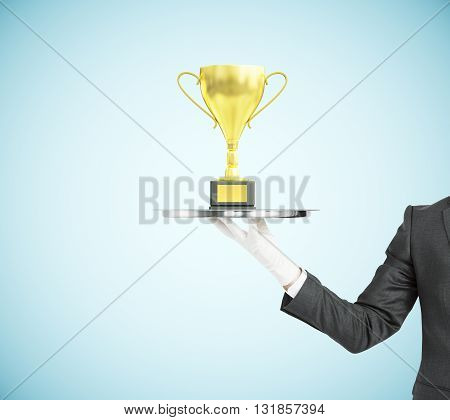 Businessman hand in white glove holding tray with golden cup trophy on blue background