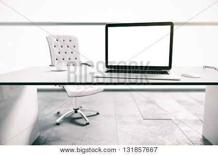 Closeup of blank white laptop screen and coffee cup on desktop in office interior. Mock up 3D Rendering