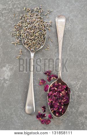 Dried Lavender and Rose petals spilling off vintage silver spoons on grey slate background