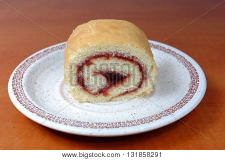 Homemade gluten-free roll with plum jam on plate on wooden table food diet