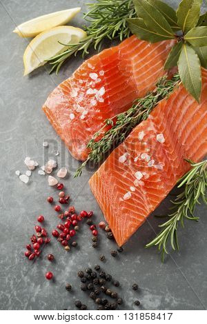 Selection of Herbs and Spices with fresh fillets of raw pink trout on a grey slate background. Ingredients includes pink salt black peppercorns fresh thyme fresh rosemary lemon wedges pink peppercorns bay leaves