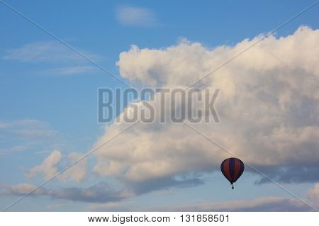 Lonely air baloon flying in front of white puffy clouds