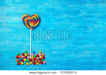 Flat Lay Of Beautiful Multicolored Lollipop Shape Heart And Sweet Bonbons On Painted Blue Wooden Bac