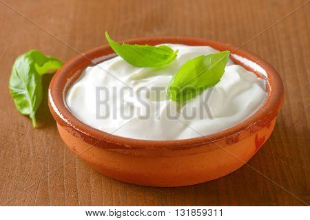 bowl of white yogurt on wooden table - close up