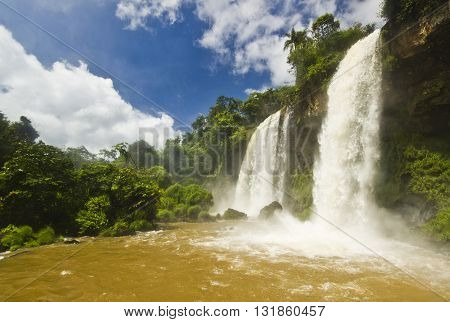 a lot of water in iguazu falls with green forest and stones surrounding