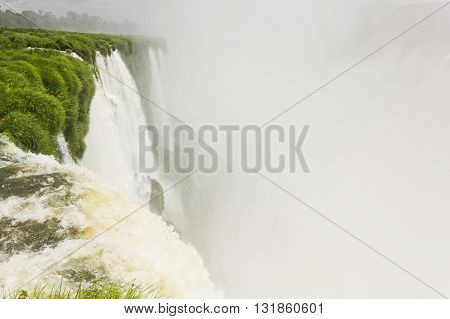 a lot of water in iguazu falls with green grass and stones surrounding with empty part in image