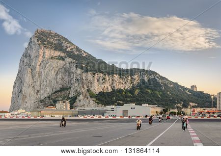 Gibraltar - March 17, 2012: View of Gibraltar rock at sunset from spanish border. Pedestrians and motorists are crossing airstrip for get into Gibraltar and back to Spain.
