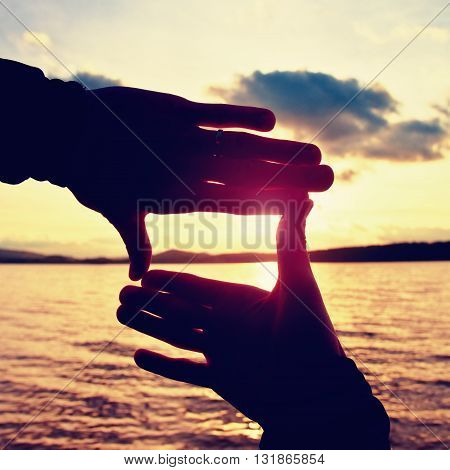 Holding Hands In Square Frame With Sunset Immersing At The Horizon. Autumn Evening At The Lake.
