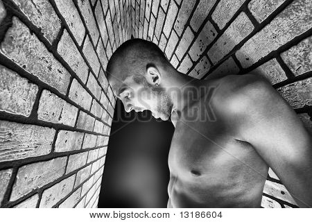 Portrait of a handsome muscular man posing over black background and brick wall.
