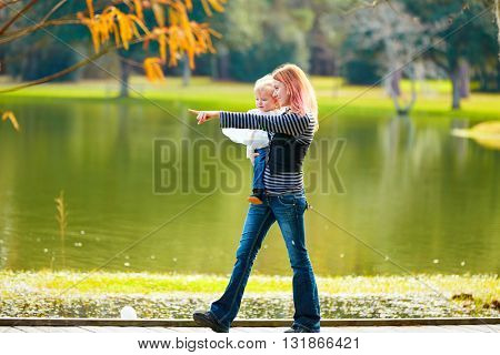 Kid girl and mother walking in the park lake pointing finger