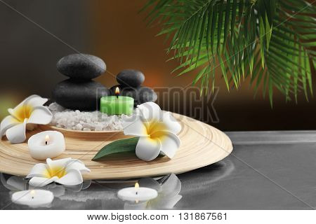 Composition with spa stones and plumeria on blurred background
