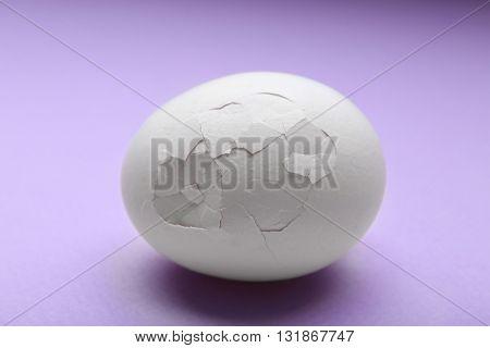 Cracked egg on purple background
