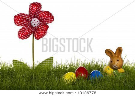 small easter bunny with easter eggs and drapery flower in grass