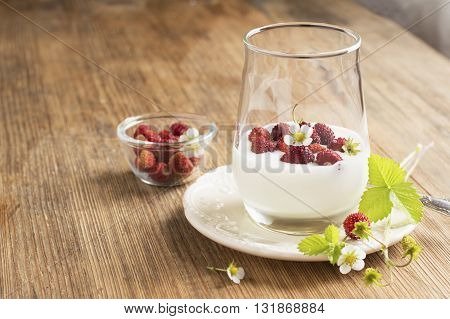 Natural yogurt with fresh strawberries for breakfast served in portions in a glass on a wooden background. The concept of a healthy natural food. selective focus