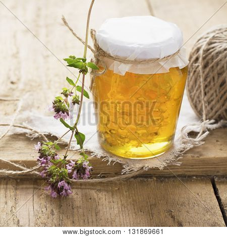 Honeycomb in a glass jar on a rustic wooden background. selective focus