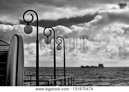 black and white photo lights and ship with cloudly sky