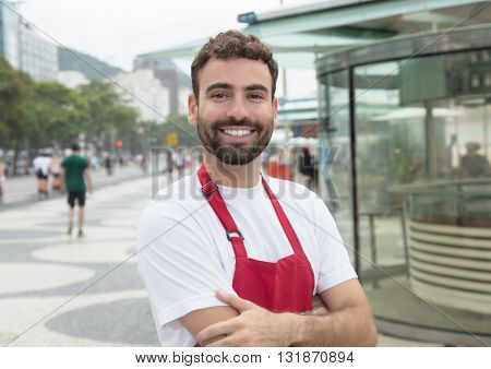 Waiter with beard and crossed arms looking at camera outdoor in front of a restaurant