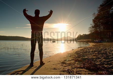 Silhouette Of The Person On A Decline Seeing Off The Sun. Slim Sportsman On Beach Shadowing Eyes .