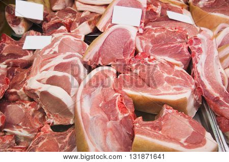 Variety of raw meat slices in a butcher shop