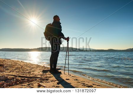 Hiker In Dark Sportswear With Poles And Sporty Backpack On Beach Enjoy Sunny Day.