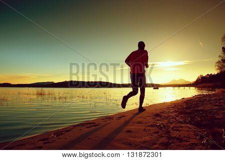 Tall Man With Pink Windcheater And Dark Cap Run On Beach At Sunset