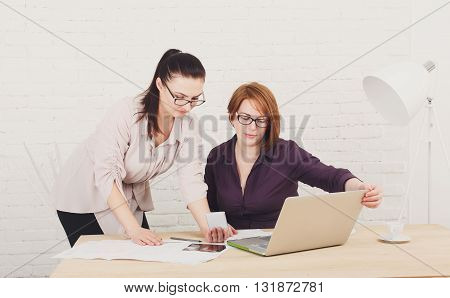 Two women in the office. Teamwork, business communication. Compare mobile version of site. Middle-aged architects designers in team work discuss project. Start up discussion. Female coworkers.