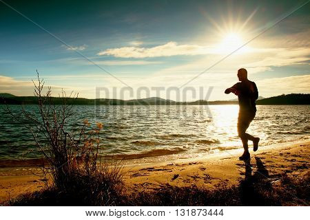 Man Athlete Checking Time During Workout Run Exercise Outdoors At Ocean Beach In Sunny Cold Morning